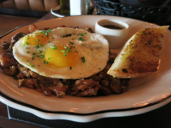 Prime rib hash is topped with a sunny egg and accompanied