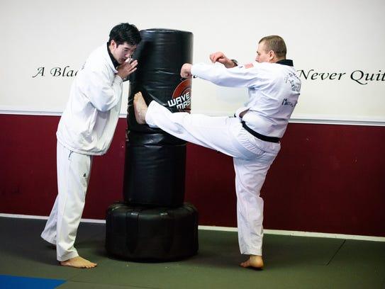 Instructor Derek So, left, encourages Robert Zerance,