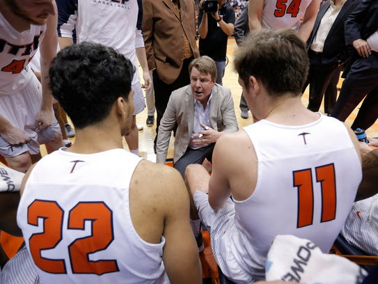 UTEP basketball coach Tim Floyd huddles with his team