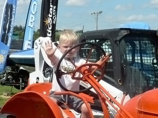 An old Allis Chalmers and young boy are a happy pair.