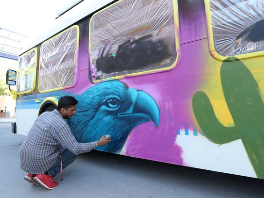 Benito Mendoza paints the side of a Sun Metro Bus during
