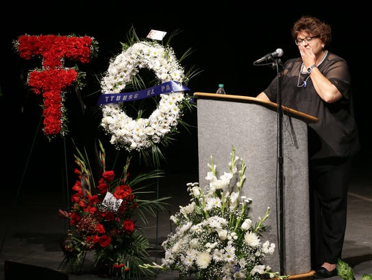 Angie Escarciga wipes a tear from her eye as she speaks