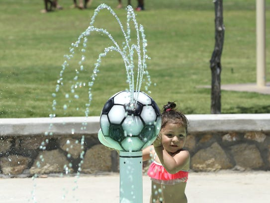 A girl cools down Tuesday at a splash pad as the temperature