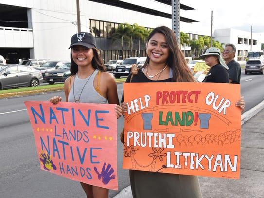 Franceska De Oro, left, and Moñeka De Oro hold signs