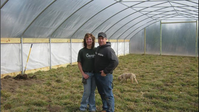 Denise (left) and John Hilgart, in their seasonal high tunnel installed in 2012