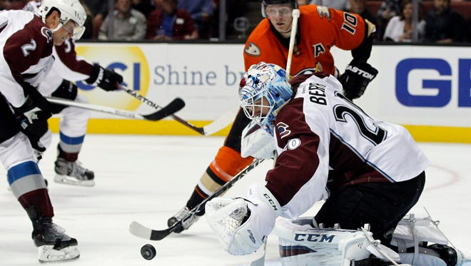 Colorado Avalanche goalie Reto Berra (20), of Switzerland stops a shot with defenseman Nick Holden (2) as Anaheim Ducks right wing Corey Perry (10) looks on during the second period of an NHL hockey game in Anaheim, Calif., Friday, Oct. 16, 2015.