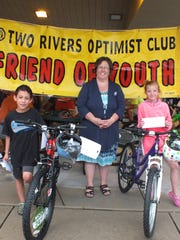 File - The Two Rivers Bike Safety Rodeo was held at Washington Park in Two Rivers in 2017. Children brought their bicycles for an equipment safety check, learned riding rules and completed a skills-guided safety obstacle course. Helmets were given to boys and girls who didn't own one. Pictured is Debbie Allie (center) representing the  Fox Communities Credit Union, which donated two bikes won by Jordan Ostram and Kelynn Davy.