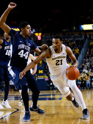 Jan 4, 2017; Ann Arbor, MI, USA; Michigan Wolverines guard Zak Irvin moves the ball defended by Penn State Nittany Lions forward Julian Moore in the first half at Crisler Center.