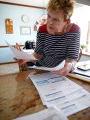 Karen Coon looks over some of her energy bills in her Lacey Township home.