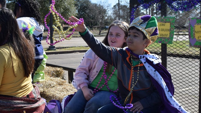 Fourth-grader Kyle Colson (far right) was crowned penny king and sixth-grader Payton Thiels (left) was crowned penny queen of the St. Frances Cabrini School Mardi Gras parade Friday. They received the distinction by bringing in the most change.