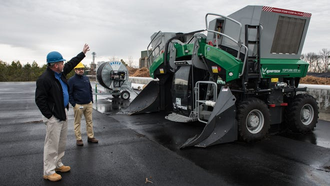 Wayne Hudson, left, Vice President of Operations for Perdue Agribusiness and Steve Levitsky, Vice President of of Sustainability for Perdue Farms explain how a compost trimmer works at the Perdue AgriRecycle facility in Blades, Del. on Thursday, Jan. 26, 2017.  This machine is used to blend compost piles consistently.