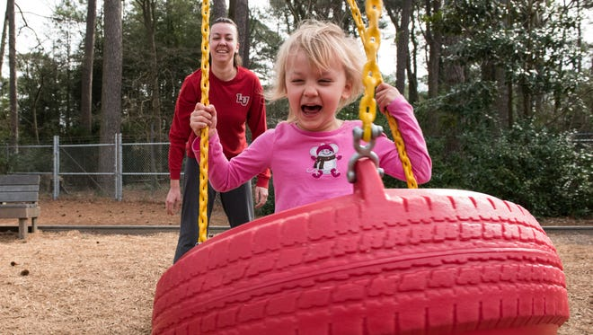 Katrina Baine, of Eden, pushes her daughter Emma, 4, on a tire swing at Ben's Red Swings on Wednesday, Feb. 8, 2017.