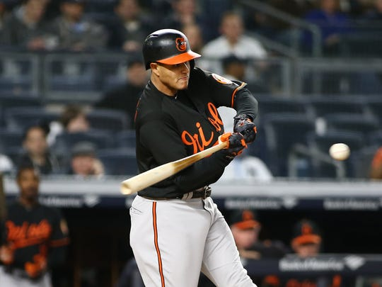 Baltimore Orioles shortstop Manny Machado (13) hits a solo home run against the New York Yankees during the third inning at Yankee Stadium.