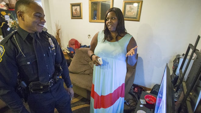 """IMPD officer Jason Mitchell chats with Kimberly Washington after giving her a $100 gift card during an operation called """"Ho Ho 5-0.""""  Officers delivered $100 gift cards on Monday, Dec. 21, 2015, to 200 people in need during the holiday season. An anonymous Indianapolis businessman donated $20,000 to the Indianapolis Public Safety Foundation for the community outreach effort."""