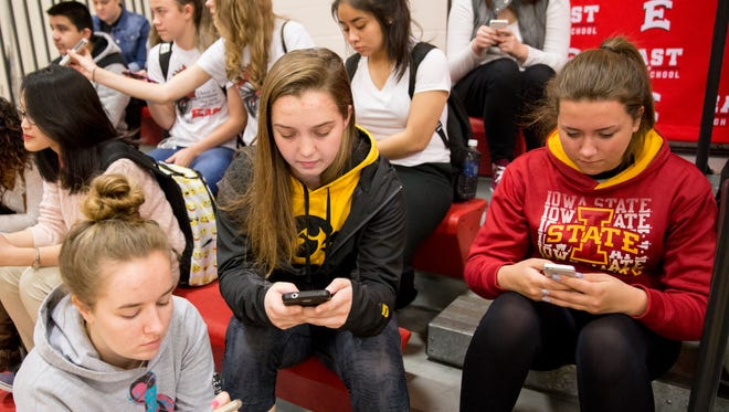 East High School students Emma Stanley, left, Jordyn Anderson, center, and Autumn Lippold start looking at Raise.me on their phones after an announcement about the website's partnership with University of Iowa at East High School in Des Moines on March 2.