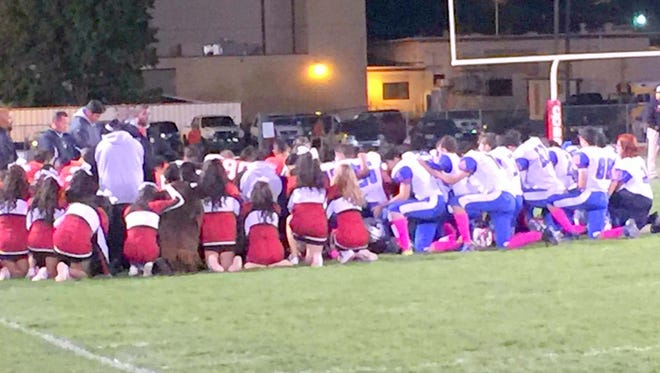 The Cobre High football team and Hot Springs High football squad pray while medical personnel are tending to Corey Roberson on the field.