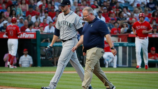 Mariners starter James Paxton walks off the field Thursday with a trainer. Paxton was removed from the game with what Mariners officials later called a back strain.