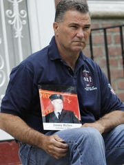 """FILE - In this May 3, 2012, file photo, Jim Riches, a retired New York deputy fire chief who responded to the 2001 terror attacks and lost his son, Jimmy, a fellow firefighter, poses for a photo with a photo of his son near his home in New York. Sept. 11 victims' relatives are greeting the news of President Donald Trump's now-canceled plan for secret talks with Afghanistan's Taliban insurgents with mixed feelings. """"I don't want to see other families suffer the way I did. That's the bottom line. Not soldiers or innocent victims of terrorism,"""" Riches said. (AP Photo/Seth Wenig, File)"""