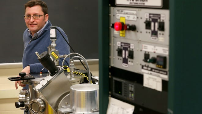 """Casey W. Miller, who heads RIT's graduate materials science and engineering program, with a magnetron sputtering tool, where alloys are made from blocks of metals. Miller's research in """"green cooling"""" uses alloys that interact with magnetic fields to cool air for potential use in a refrigerator."""