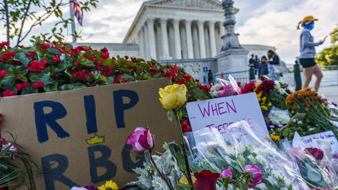 Officials stand on the Supreme Court steps on Capitol Hill in Washington Tuesday as preparations take place for a private ceremony and public viewing in remembrance of Justice Ruth Bader Ginsburg.