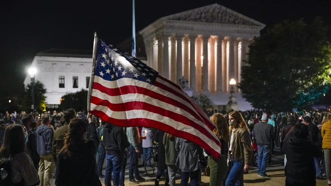 People gather at the Supreme Court in Washington, D.C. Saturday night to honor the late Justice Ruth Bader Ginsburg, one of the high court's liberal justices, and a champion of gender equality. Her death leaves a vacancy that could be filled with a more conservative justice by President Donald Trump.