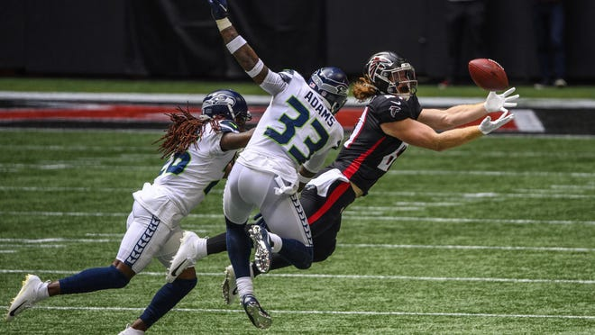 Falcons tight end Hayden Hurst (81) catches a pass as Seattle Seahawks strong safety Jamal Adams (33) and cornerback Shaquill Griffin (26) defend during the first half Sunday in Atlanta.