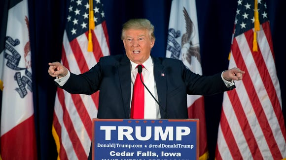 Donald Trump points to the crowd while speaking at