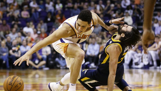 Phoenix Suns  Devin Booker makes contact with Utah Jazz Ricky Rubio in the first half on Oct. 25, 2017 at Taking Stick Resort Arena in Phoenix, Ariz.