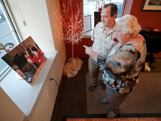 Nancy and Wayne Christman look at a photo of themselves attending a memory cafe during the celebration of the fifth anniversary of the Fox Valley's first memory cafe on Wednesday in Appleton.