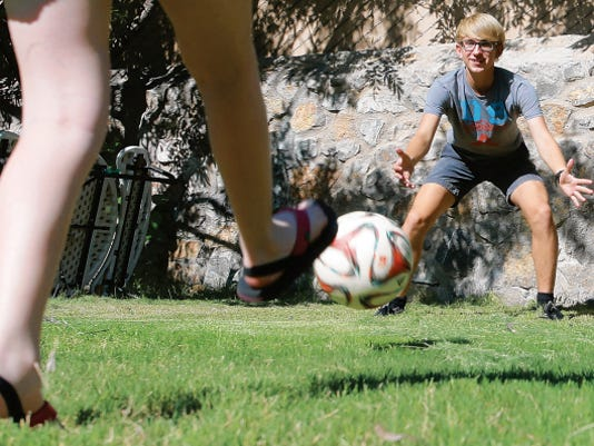 VICTOR CALZADA-EL PASO TIMES Exchange student Alexander Pahlitzsch defends against a soccer kick by Gianna Morron Wednesday.