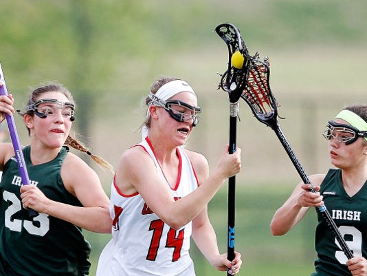 York Catholic's Amanda Tufano, left, and Maura Palandro, right, stay close as Susquehannock's Gena Speights, center, moves the ball down the field during the York-Adams League lacrosse semifinal game at Central York High School on Tuesday.