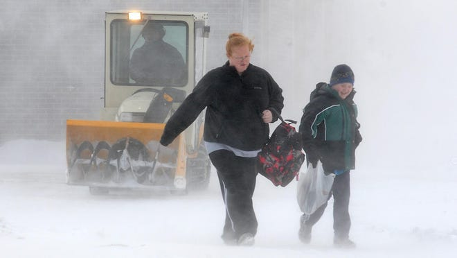A parent and student leave a school in whiteout conditions on Wednesday, Jan. 22, 2014, in North Mankato, Minn., after high winds and frigid temperatures prompted officials to dismiss classes early.