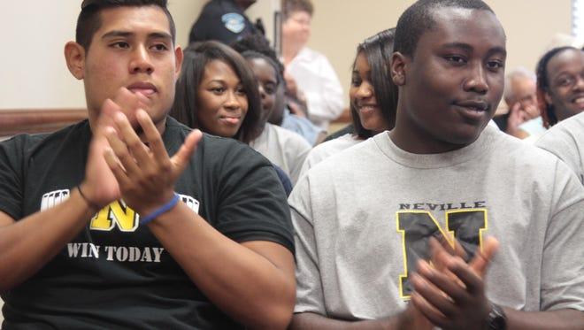 Armanda Che and Tyler Johnson both Neville High School students applaud as the Monroe City School Board approves renovations for their school at Thursday's meeting.