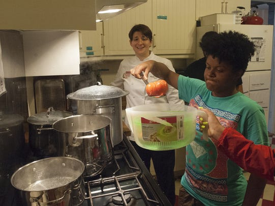 CFET's teenage farmer Kierra Suarez and Campbell's Chef, Carrie A. Welt, left, prepare a tomato gazpacho soup made with Campbell's tomatoes at the Environmental Transformation home in Camden.