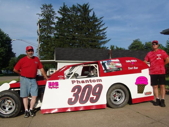 """Norm """"Stormin' Norman"""" Aronhalt, left, and Tracy Wyler stand by the Phantom 309 Ray Border Memorial Race Car."""