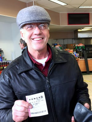 David Berka, of Binghamton, shows off the Powerball ticket he purchased Monday afternoon in Johnson City.