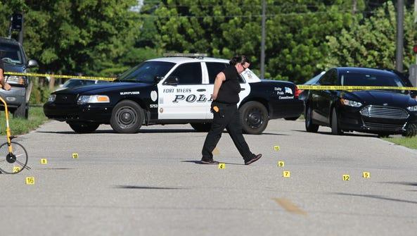 Crime scene investigators comb through the scene of
