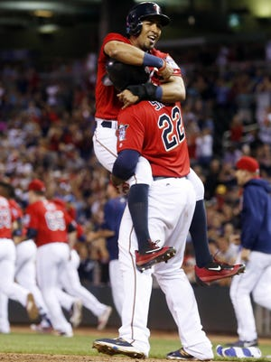 The Minnesota Twins' Eddie Rosario is hoisted up by Miguel Sano after he scored the winning run on a bases-loaded walk by Chicago White Sox pitcher Tommy Kahnle during the 12th inning Friday in Minneapolis. The Twins won 2-1.