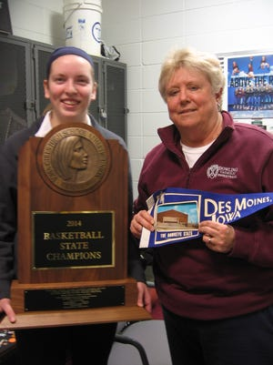 Sharon (Tyler) Hanson, right, holds a banner from her 1965 state championship season. Dowling senior Amber Gierstorf holds her team's state championship trophy from last year.