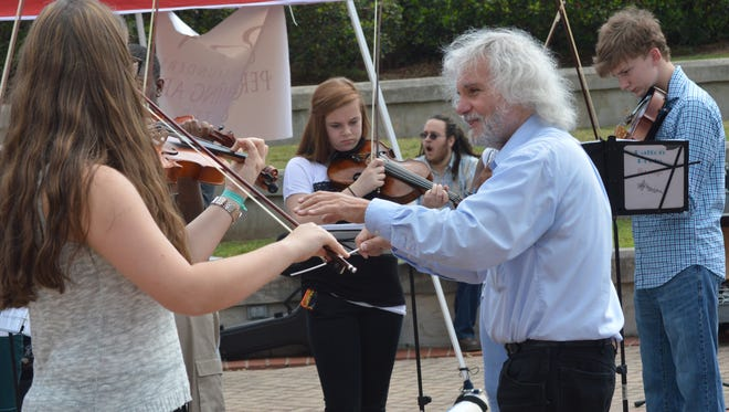 John Dechiaro (right) directs members of the youth string orchestra in a performance at a past Alex River Fête.