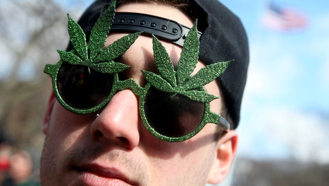 Alex Saling of Detroit shows off his sunglasses during the 2014 Hash Bash at the University of Michigan in Ann Arbor.