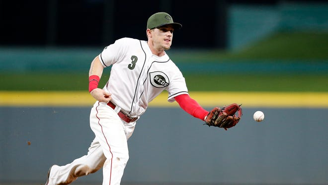 Cincinnati Reds second baseman Scooter Gennett (3) flips a ground ball to first baseman Brandon Dixon in the top of the ninth inning of the MLB National League game between the Cincinnati Reds and the Arizona Diamondbacks at Great American Ball Park in downtown Cincinnati on Friday, Aug. 10, 2018. The Reds won the series opener, 3-0.