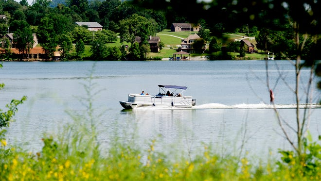 A boat floats down the Emory River past TVA Lakeshore Park in Harriman, Tennessee on Tuesday, July 11, 2017.