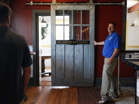 Crabby Dick's owner John Buchheit shows off the new barn door to his partner Dale Slotter. The restaurant in Delaware City is preparing to reopen on June 9 following renovation work that includes a new bar and kitchen area.