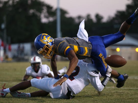 Wakulla's Kelton Donaldson knocks the ball out of Rickards' D.J. Phillips, causing a touchback as the ball rolled out of bounds in the endzone during their game at Cox Stadium on Thursday night.