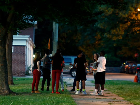 Young people congregate on Ferris Street at Woodlawn Park in Wilmington before 9 p.m. Monday.