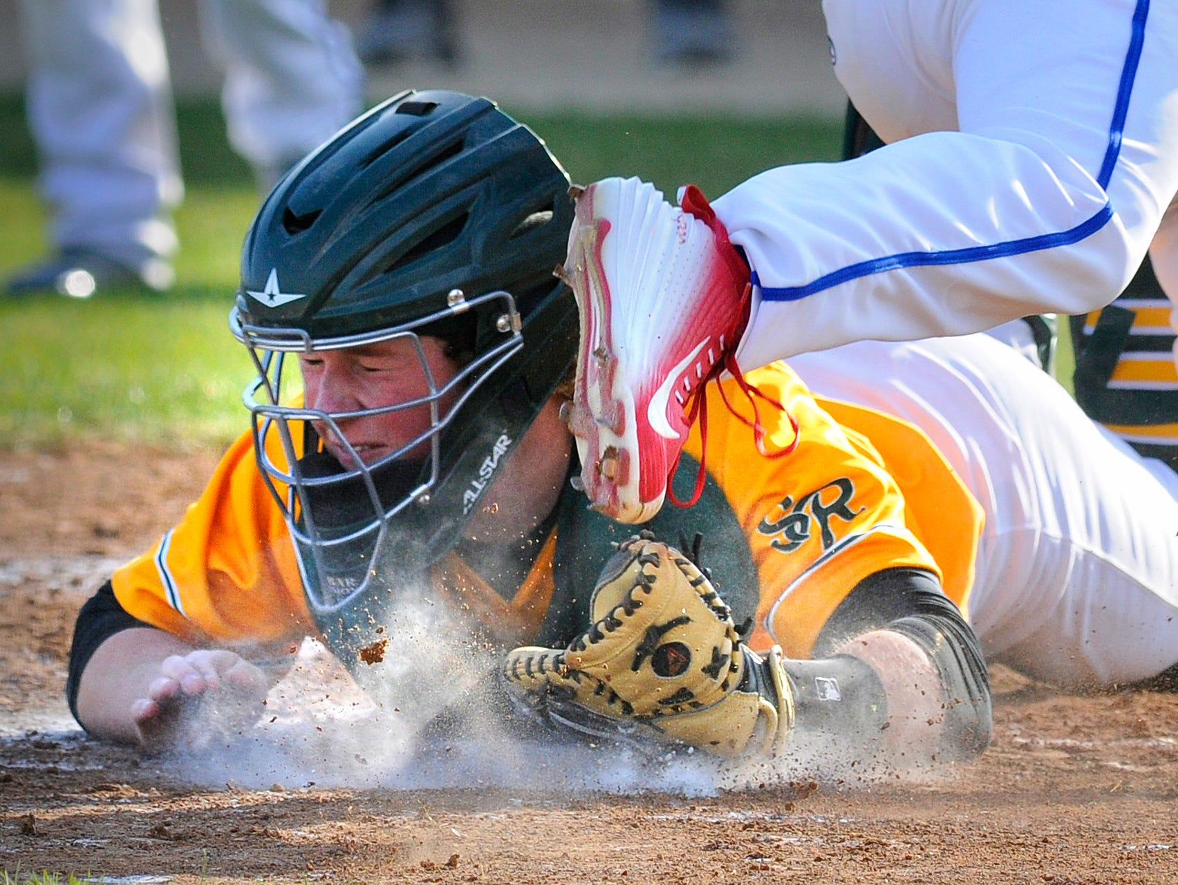 Catcher Eric Burski of Sauk Rapids tries to make a tag on a St. Cloud Apollo baserunner during Thursday's game in Sauk Rapids.