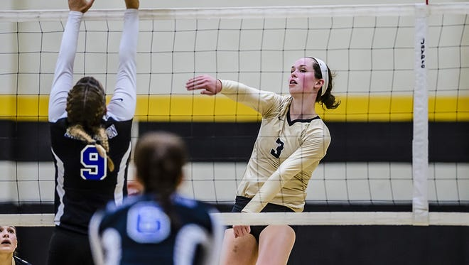 Meredith Norris, 3, of Corunna hits through a block by Allison Petts, 9, of Lake Fenton in the 3rd set of their match Tuesday September 13, 2016 in Corunna.  Norris is one of 10 finalists for Michigan Miss Volleyball.