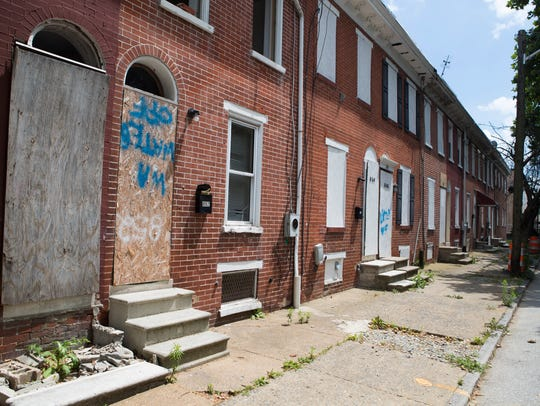 Vacant homes stand boarded up on the 800 block of Bennett