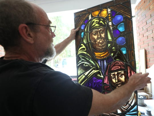 Bill Dodds, a stained glass master craftsman, works